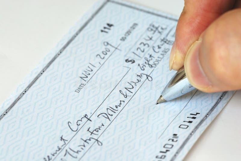 Scrivendo un assegno alla fattura di paga fotografie stock