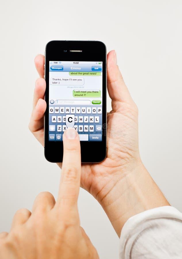 Scrivendo un messaggio di testo sul iPhone 4 fotografia stock