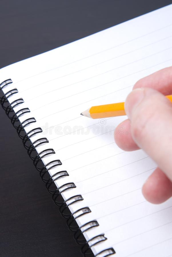 Scrivendo in un blocco note a spirale in bianco immagini stock libere da diritti