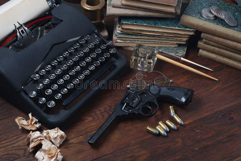 Scrivendo una storia di romanzo di crimine - vecchie retro macchina da scrivere e pistola d'annata del revolver con le munizioni, fotografia stock libera da diritti