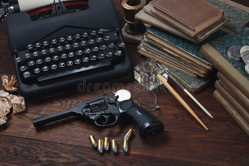 Scrivendo una storia di romanzo di crimine - vecchie retro macchina da scrivere e pistola d'annata del revolver con le munizioni, fotografia stock