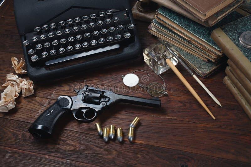 Scrivendo una storia di romanzo di crimine - vecchie retro macchina da scrivere e pistola d'annata del revolver con le munizioni, immagine stock libera da diritti