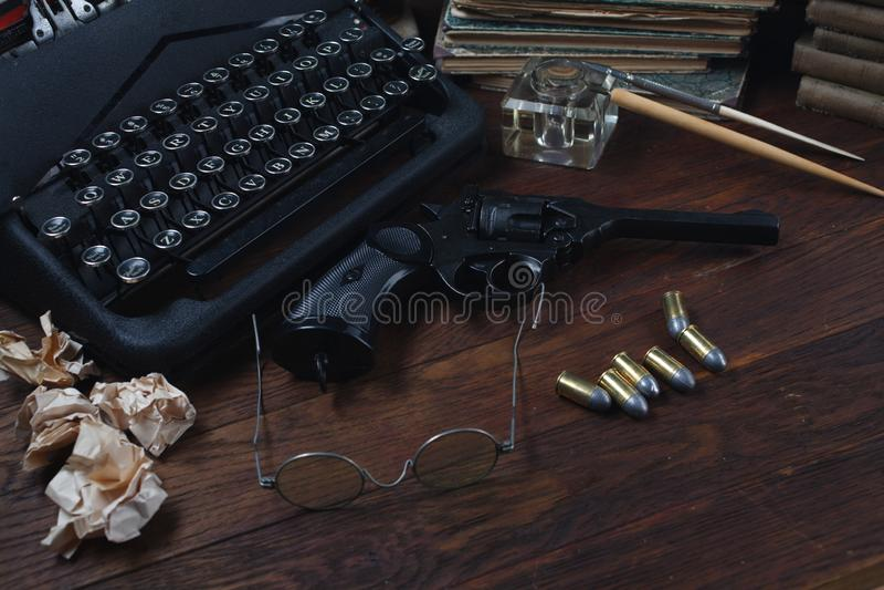 Scrivendo una storia di romanzo di crimine - vecchie retro macchina da scrivere e pistola d'annata del revolver con le munizioni, immagini stock libere da diritti