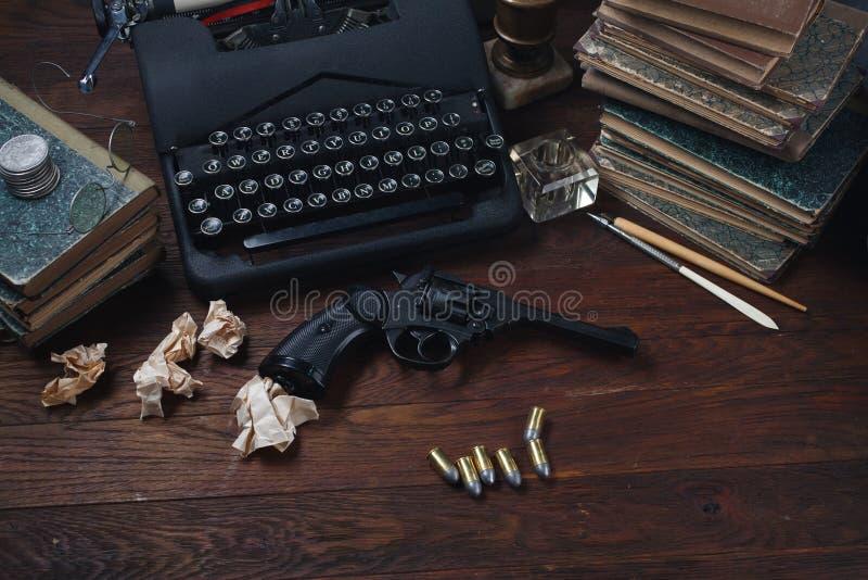 Scrivendo una storia di romanzo di crimine - vecchie retro macchina da scrivere e pistola d'annata del revolver con le munizioni, fotografie stock