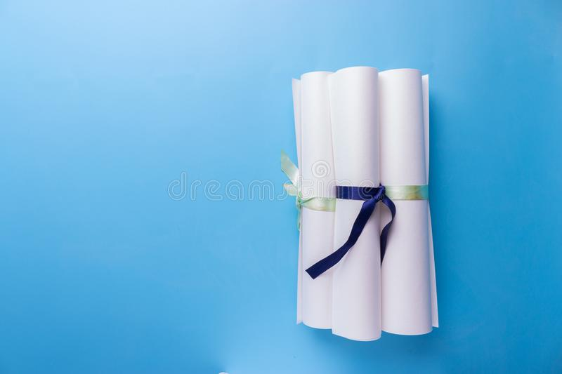 Scroll of paper with ribbon on a wooden surface. Scroll of paper with a blue ribbon on a wooden surface royalty free stock photography