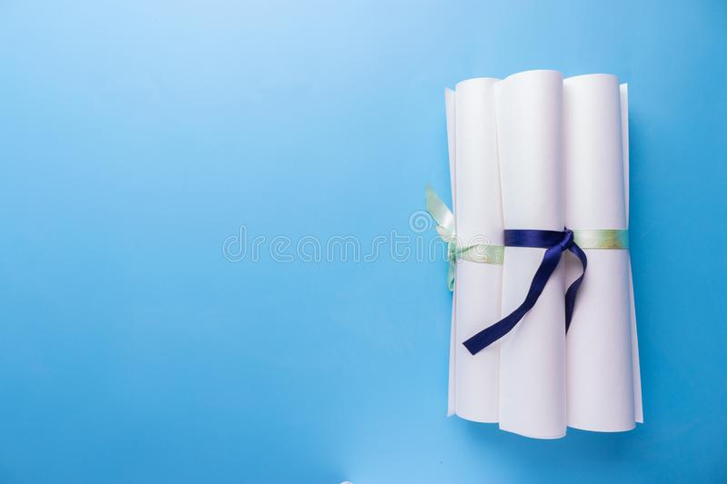 Scroll of paper with ribbon on a wooden surface. Scroll of paper with a blue ribbon on a wooden surface stock images