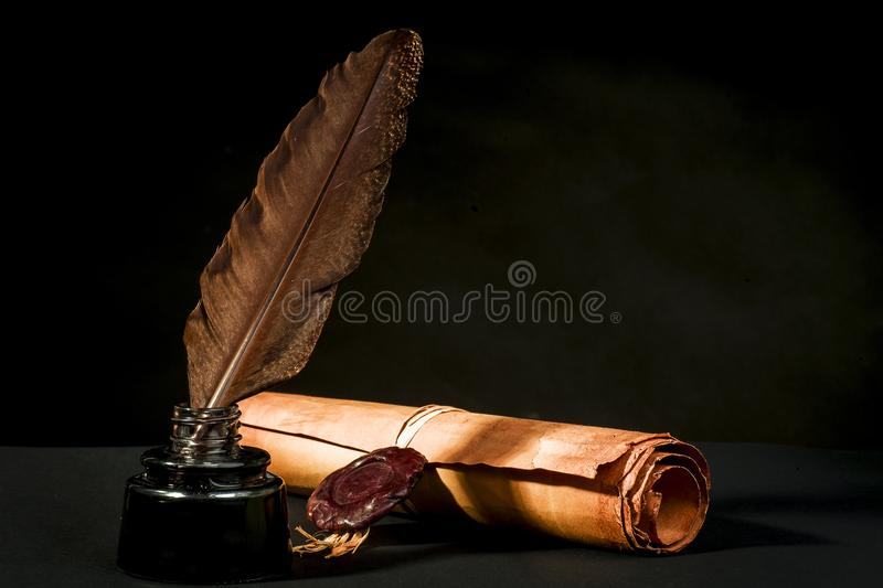 Scroll of a papyrus with a seal, a feather and an inkwell royalty free stock images