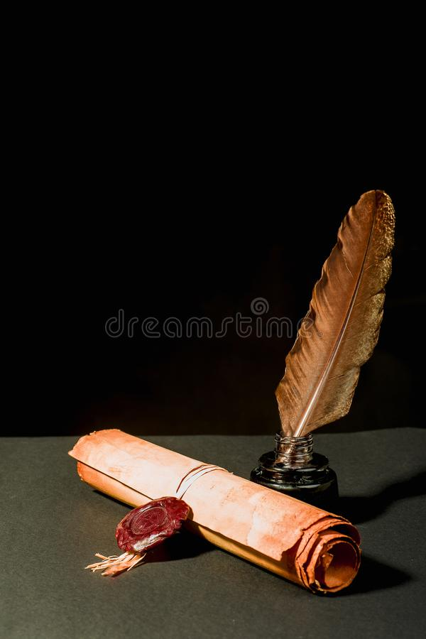Scroll of a papyrus with a seal, a feather and an inkwell stock image