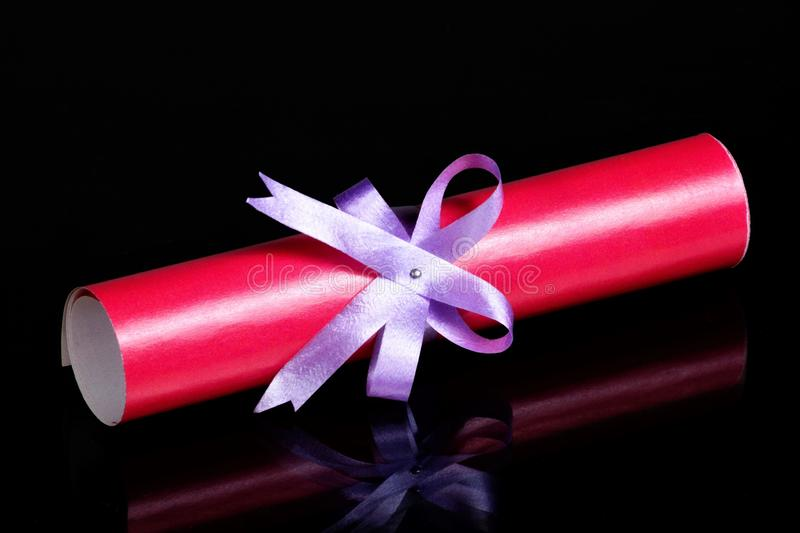 Scroll sheet in roll and ribbon with bow. Red diploma is a document of a graduate student, a certificate of graduation from a. University, College and obtaining stock photos