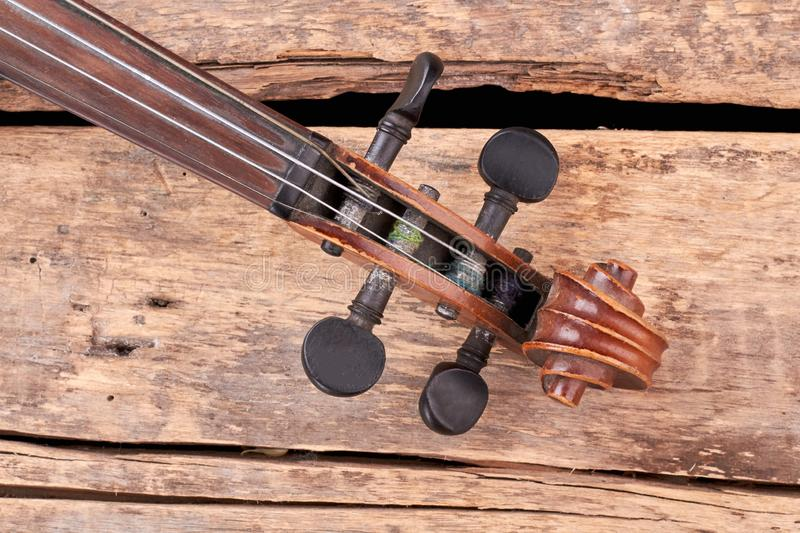 Scroll of the violin on wooden boards. stock photo