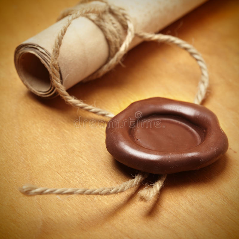Scroll with wax seal. On a wooden table stock images