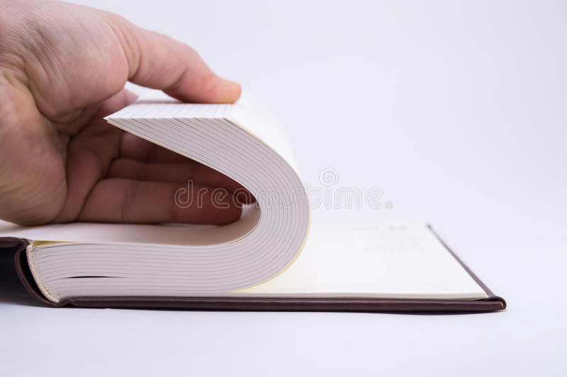 Scrolling pages, documentation. Hand scrolling blank pages of notebook stock photography