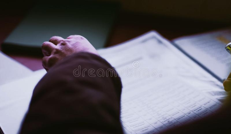 Scrolling through a sheet of paper. Hands of a man over a sheet of paper. stock photo