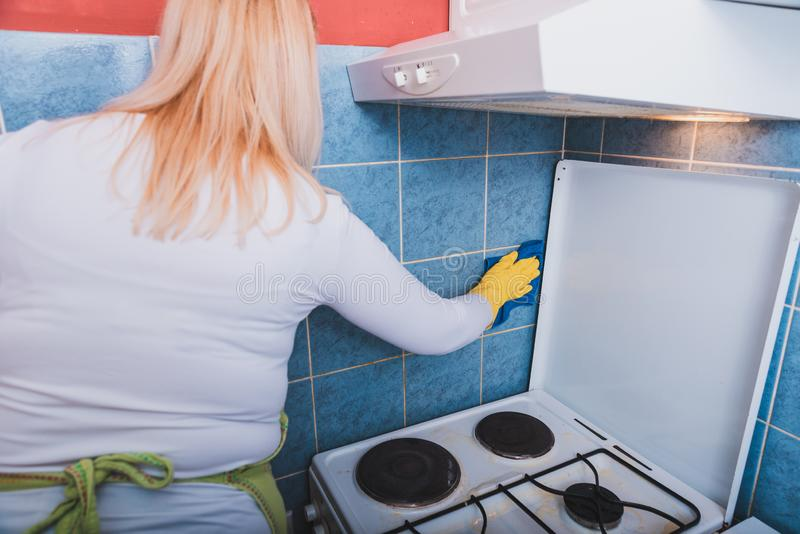 Scrubbing the tiles in the kitchen with a sponge royalty free stock photography
