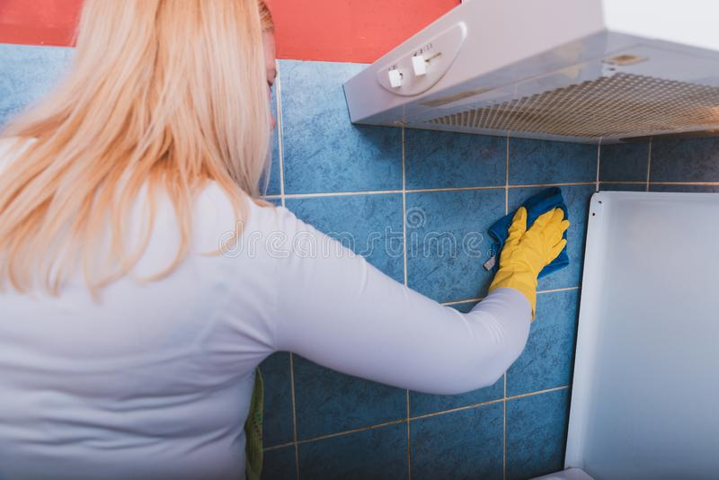 Scrubbing the tiles in the kitchen with a sponge stock image