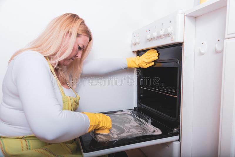 Scrubbing the tiles in the kitchen with a sponge. Scrubbing dirty tiles in the kitchen with a sponge in a yellow gloves royalty free stock photo