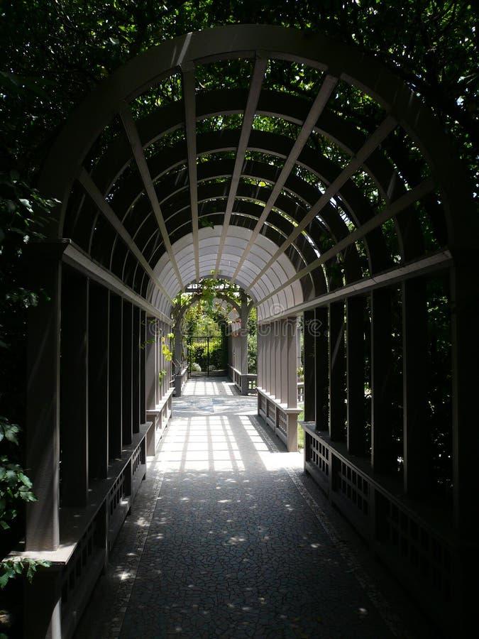 Scrutando attraverso un arco del giardino fotografie stock libere da diritti