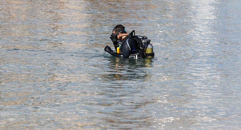 Scuba diver adjusting regulator before diving stock photography