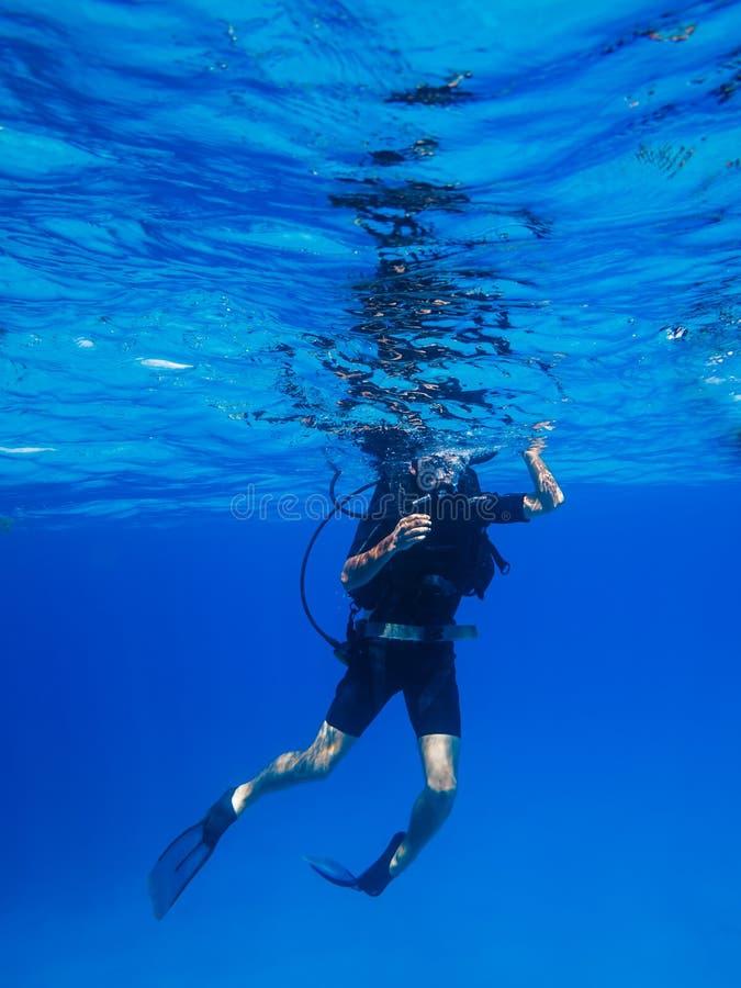 Scuba diver descends in blue water royalty free stock photos