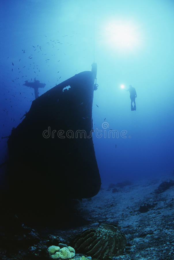 Scuba Diver Exploring Sunken Ship stock images