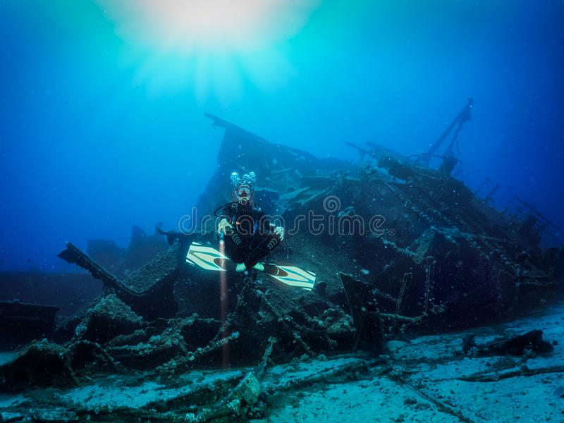 Scuba diver in front of a sunken shipwreck. A scuba diver is posing in front of a sunken shipwreck in the deep, blue sea stock image