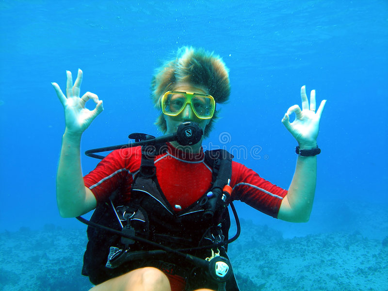 Scuba diver gives a big Okay. A colourful scuba diver gives a big Okay to her buddy during a bright dive in the Cayman Islands stock images