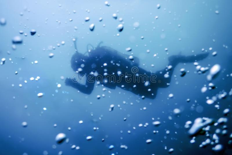 Scuba Diver Swimming on a Blue Water Air Bubbles. Underwater royalty free stock photography