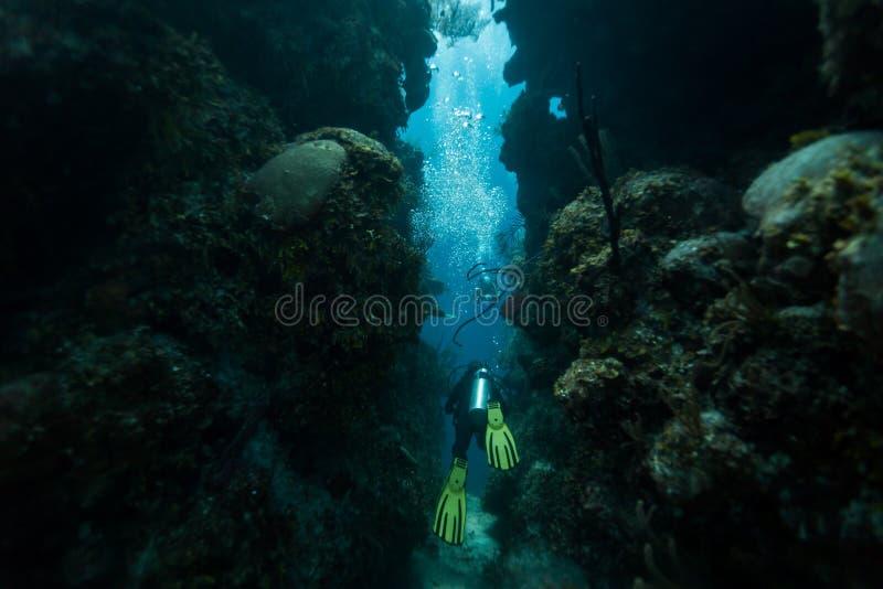 Scuba diver swims through tunnel stock photo
