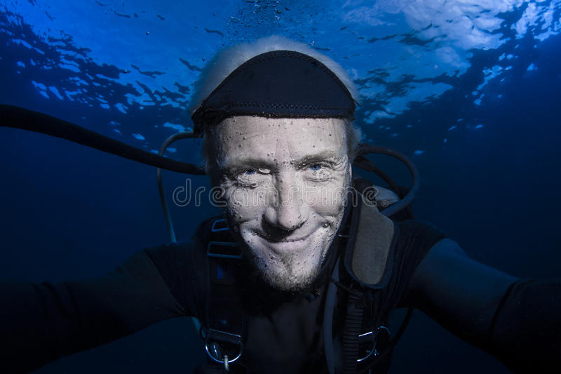 Scuba diver underwater on blue background in the ocean stock photo