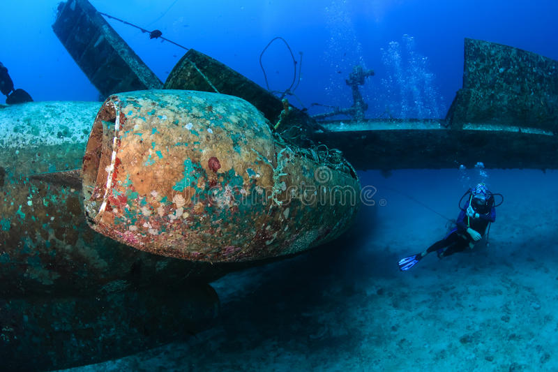 SCUBA divers around an aircraft wreck. SCUBA diver swimming next to the jet engine attached to the wreckage of a sunken aircraft royalty free stock photos