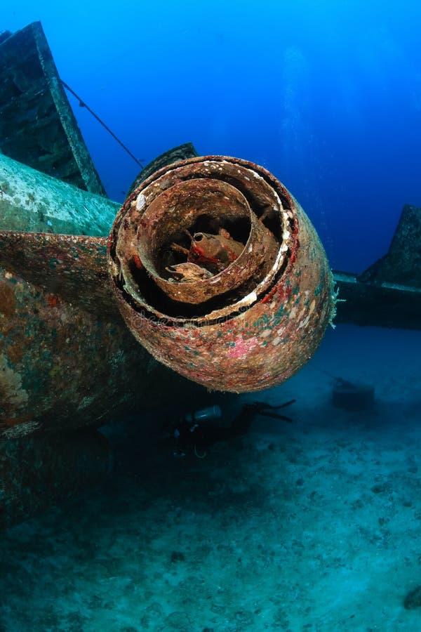 SCUBA divers around an underwater plane. SCUBA diver under the jet engine of an underwater plane wreck stock photography