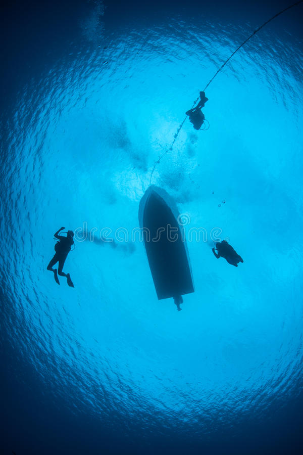 Scuba Divers Descending into Blue Water royalty free stock photography