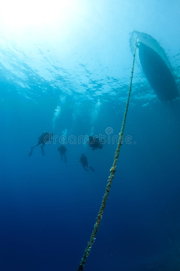 Scuba divers dive together with boat in frame