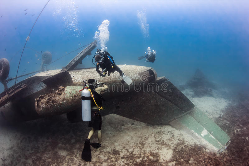 SCUBA divers explore the wreck of an aircraft. SCUBA divers exploring the upturned fuselage of an underwater aircraft wreck stock image