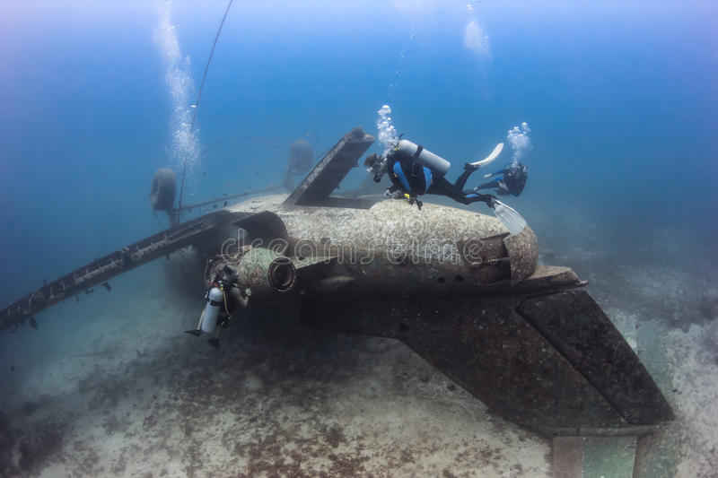 SCUBA divers explore the wreck of an aircraft. SCUBA divers exploring the upturned fuselage of an underwater aircraft wreck stock photography