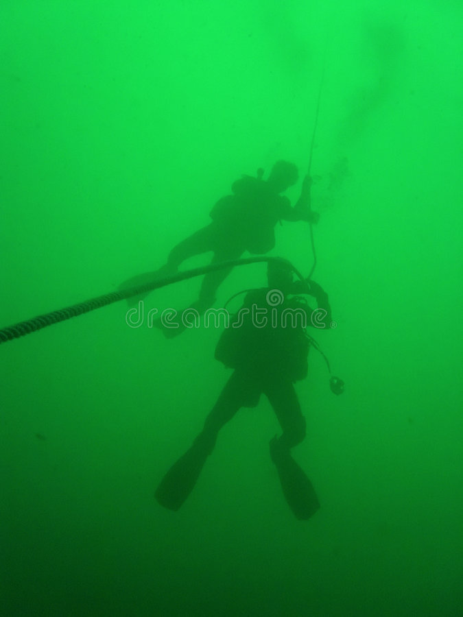 scuba divers green water diving royalty free stock image
