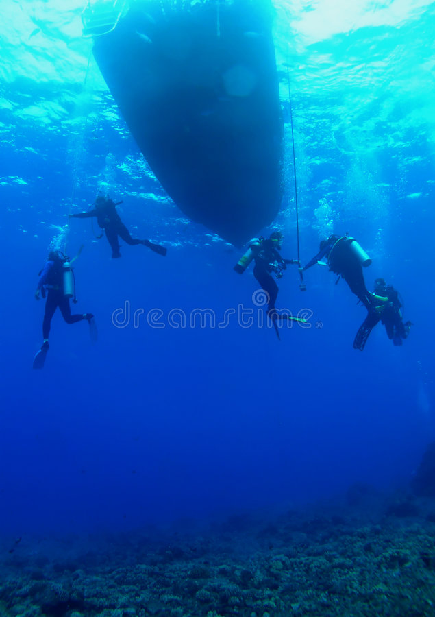Scuba Divers on a Safety Stop. Divers on a safety stop getting ready to board the boat stock photography