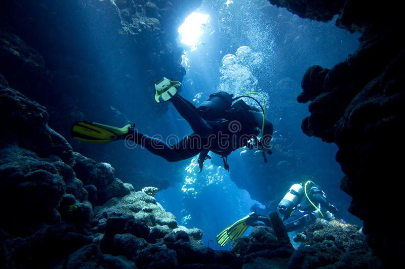 Scuba divers in underwater cave stock image