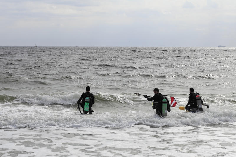 Scuba Divers Walking into the Ocean royalty free stock photos