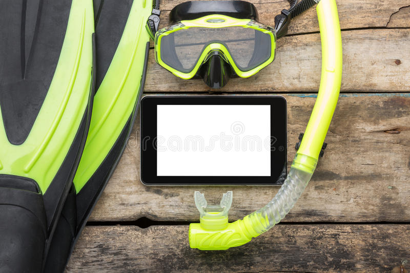 Scuba diving or snorkelling lesson template mock-up background. Flippers, mask, snorkel with blank tablet PC on wood background royalty free stock photo