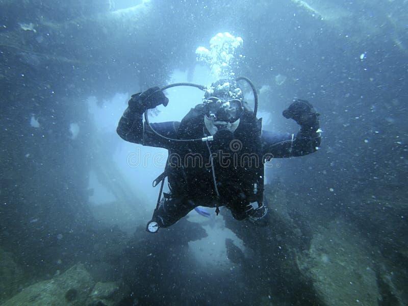 Scuba-duiker die de binnen onderwaterschipbreuk onderzoeken stock foto
