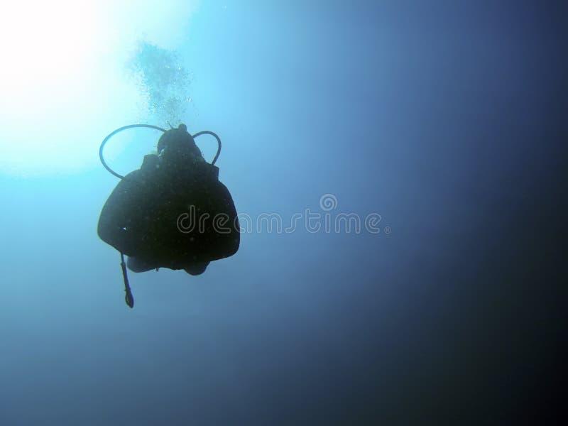 Scuba-duiker onderwatersilhouetten tegen zon royalty-vrije stock afbeelding