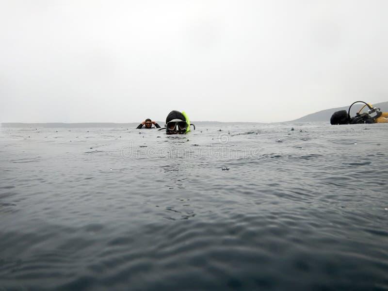 Scuba-duikers op de oppervlakte Regenachtige dag stock foto