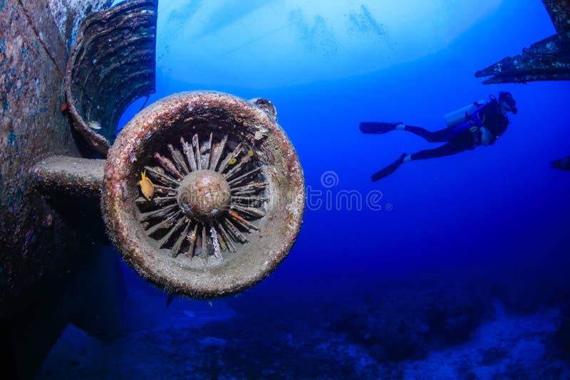 Scuba-duikers rond de straalmotor van een onderwatervliegtuigenwrak royalty-vrije stock fotografie