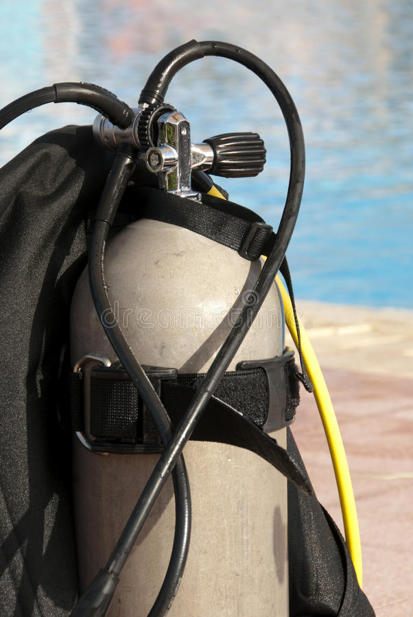 Scuba oxygen tank. Close up of a oxygen tank - diving equipment near a swimming pool stock image