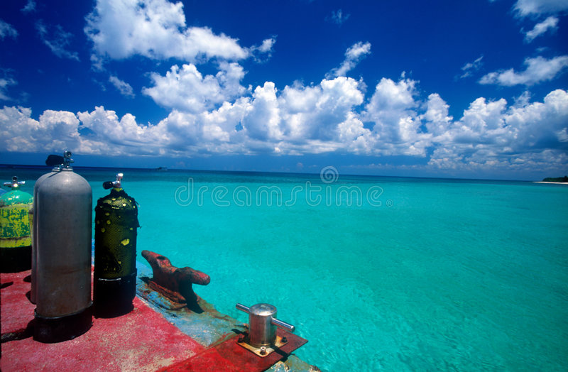 Scuba tanks by the sea. Two scuba tanks on the dock ready for a dive with turquoise blue ocean beyond stock images