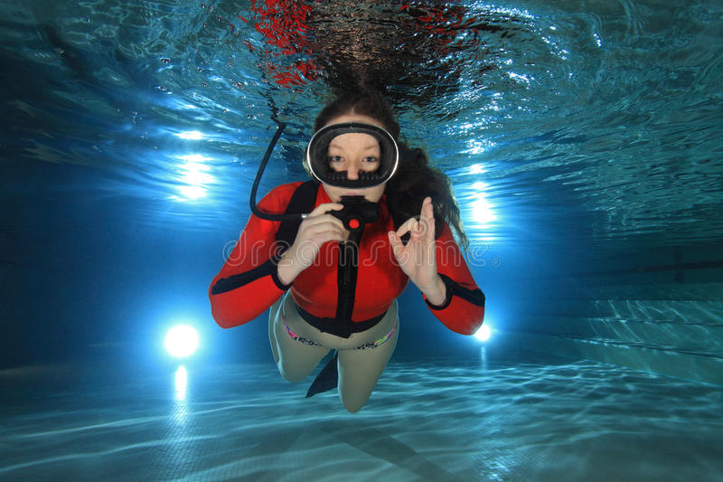 Scuba woman underwater. Scuba woman diving with red neoprene suit underwater in the pool royalty free stock image