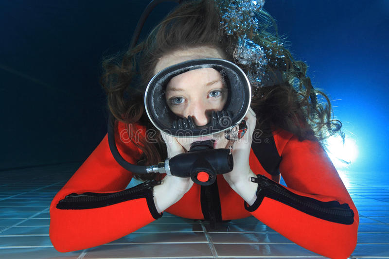 Scuba woman underwater. Scuba woman diving with red neoprene suit underwater in the pool stock photos