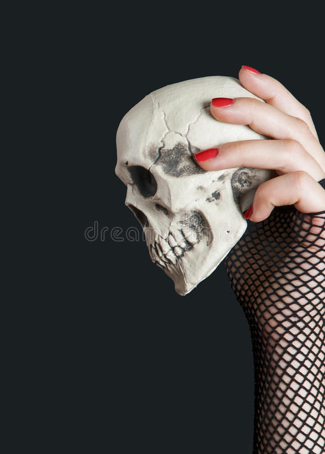 Scull in the hand on black background. Scull in the hand with red nails on black background stock photos