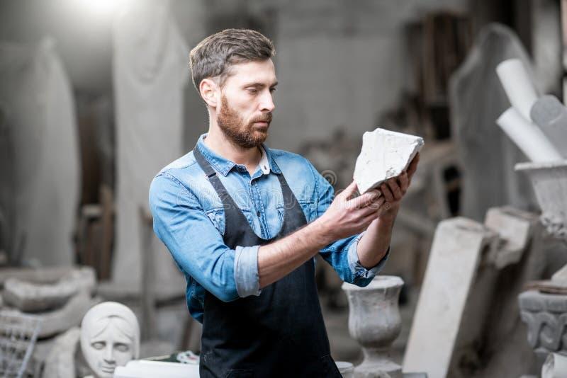 Sculpteur avec un morceau de pierre dans le studio images stock